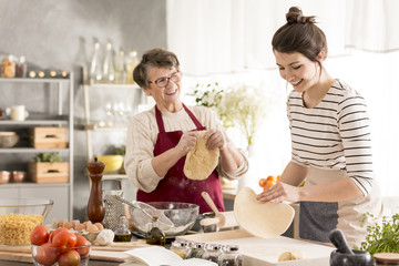 Grandmother preparing pizza with granddaughter