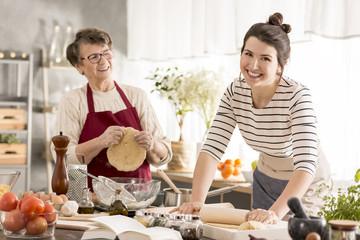 Happy woman rolling dough
