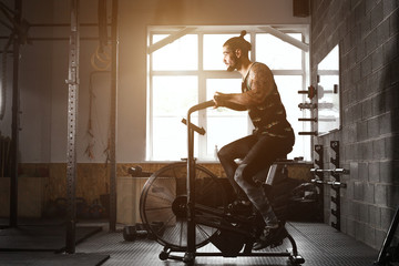 young man using exercise bike at the gym. Fitness male using air bike for cardio workout at crossfit gym.