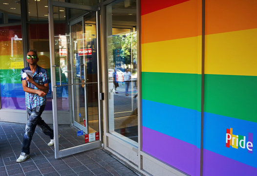 A customer leaves a branch of BMO adorned with colours of the Pride rainbow flag symbolizing gay rights, in downtown Toronto