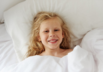 Smiling lovely girl lying in bed in the morning. Concept of comfort and relaxation.