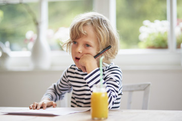 Young boy sitting at table holding pen, thinking