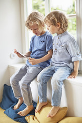 Two young brothers, sitting in window seat, looking at digital tablet