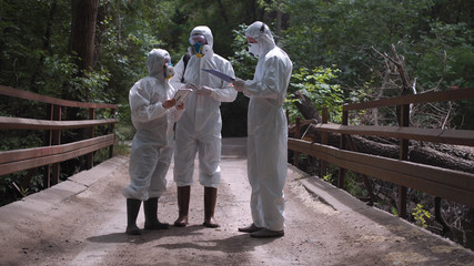 Three men in biohazard suits and masks standing on a bridge over a stream preparing to sample the water for contaminants