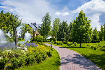 Landscaping in the garden. The path in the garden.Beautiful backyard landscape design,Some flowers and nicely trimmed bushes on the leveled front yard,Landscape formal