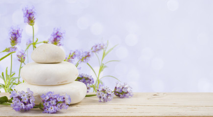 Lavender flowers and stones on wood over abstract lilac background