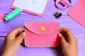 Child made a felt purse. Small child holds a pink felt purse in his hands. Craft supplies on a wooden table. Fun and easy sewing project for kids