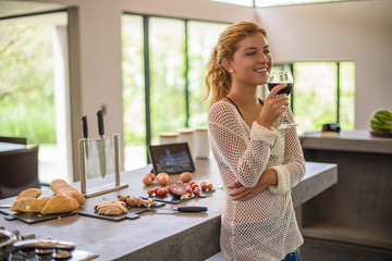 Young woman drinking red wine whilst preparing food in kitchen