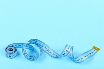 Roll of blue tape measure untwisted on turquoise background