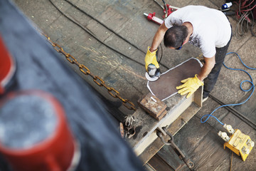 High angle view of worker preparing steel in shipyard workshop