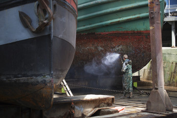 Shipyard worker cleaning boat hull with high pressure hose
