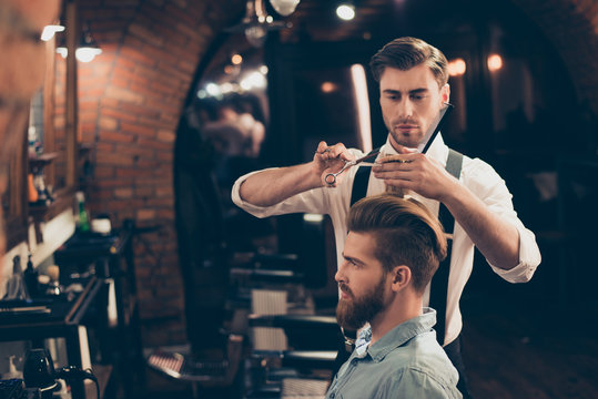Profile view of a red bearded stylish barber shop client. He is getting his perfect trendy haircut from a classy dressed handsome stylist, looking in a mirror and waiting for result