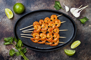 Grilled spicy lime shrimp skewers with creamy avocado garlic cilantro sauce. Top view, overhead, flat lay