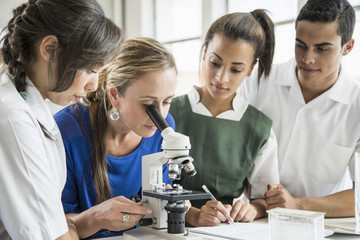 Students watching teacher use microscope in lab