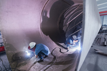 Two male welders working in industrial pipe at crane factory, China