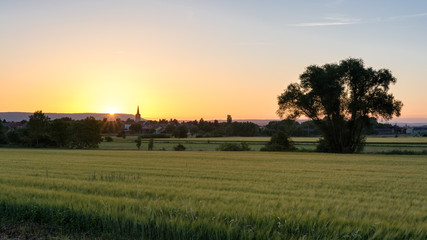French countryside - Lorraine. A small village with church surrounded by wheat fields with hills in the background at sunset