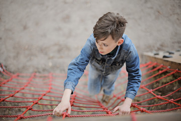 Teenager boy climbing a rope net outdoor on the kid playground. The climber trains simulator on the street.
