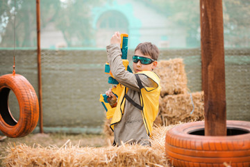 Young boy with blaster attack and play with friends in protective glasses. Excited Child with darts toy gun on the play field