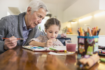 Girl and grandfather painting at kitchen table