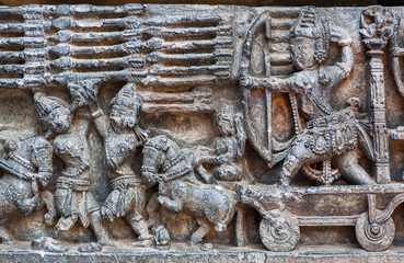 War scene with army of soldiers with bow, arrows and other weapon on the relief of Hindu temple wall. Artwork of 12th centur Hoysaleshwara temple in Halebidu, India.