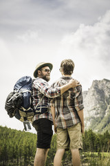 Rear view of father carrying backpack, arms around son trekking, Red Lodge, Montana, USA