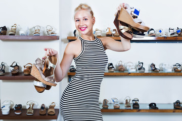 Woman standing in boutique and having many shoes