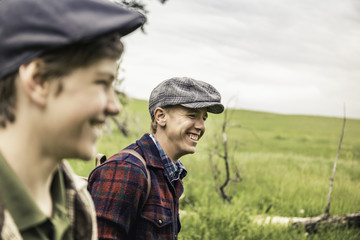 Boy and man wearing flat caps in field looking away smiling