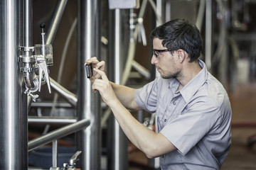 Side view of young man in brewery using smartphone to take photograph
