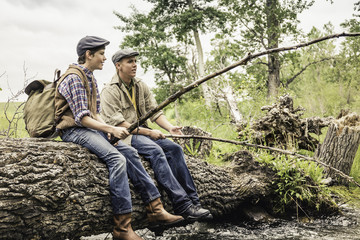 Man and boy wearing flat caps sitting on fallen tree across river fishing with branches