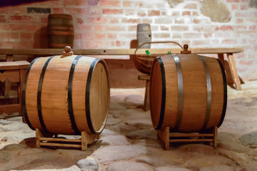 Old wine cellar with oak barrels, equipment for wine production on brick wall background.