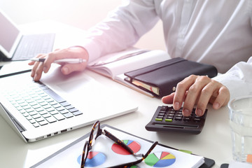 businessman hand working with finances about cost and calculate  and latop with mobile phone on withe desk in modern office