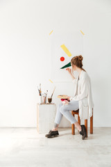 Concentrated young caucasian lady painter