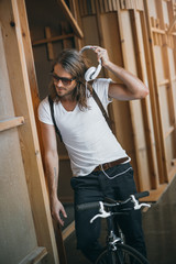 Handsome young man sitting on bicycle adjusting headphones and looking down