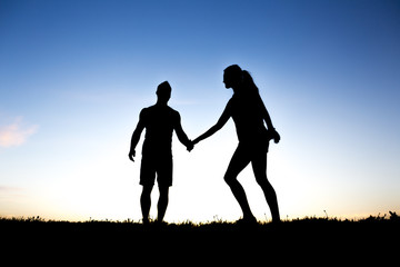 silhouette of a couple dancing against blue sky