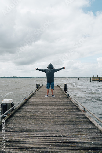 4ddbde58d828 Back view of girl with open arms wearing a hoodie on wooden pier a cloudy  summer