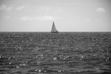 Lonely sailboat in the sea on the horizon in dark color, shine and radiance of water