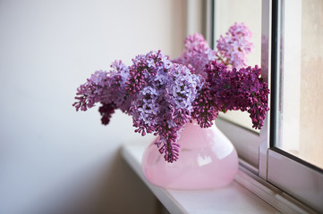 Wall Murals Lilac Purple branch of lilac in the pink vase.a delicate and beautiful flower.