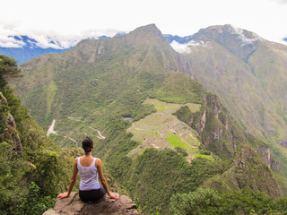Woman at the top of Wayna Picchu mountain in Machu Picchu, Peru