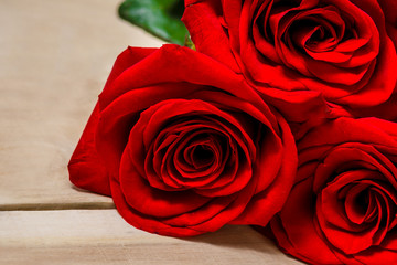 Red roses lying on a wooden table