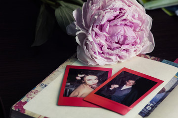 Snapshots of a young couple lying on a vintage diary. Pink wilted blurred peony on the background. Fading memories concept. Nostalgia and love.