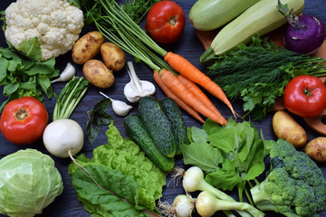Composition on a dark background of organic vegetarian products: green leafy vegetables, carrots, zucchini, potatoes, onions, garlic, tomatoes. Top view. Flat lay.