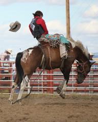Cowboy riding a saddle bronc at a rodeo