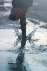 kid jumping in puddles