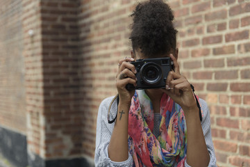 Young woman taking picture with digital camera against brick wall