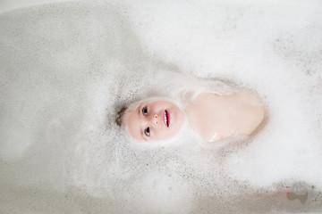 Girl lying in bathtub