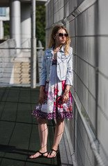 Stunning female model wearing stylish denim jacket, trendy sunglasses, and colored vibrant dress. Urban fashion blogger posing with a trendy 2017 summer look.
