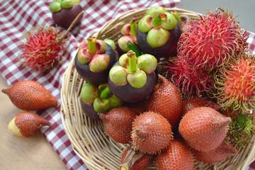 Tropical fruits in a basket, rambutan, salacca (palm fruit) and mangosteen