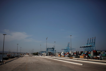 A parking for trucks is seen empty next to idle cranes during the first day of a 48-hour nation-wide strike of dockers in the port of Algeciras