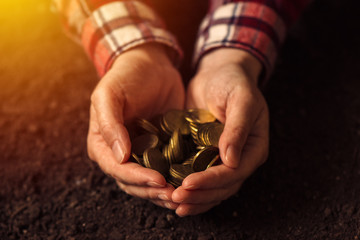 Farmer with handful of coins over soil land