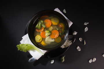 Vegetable soup in a black plate